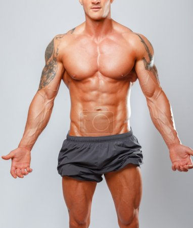 Muscular man poses showing his body.