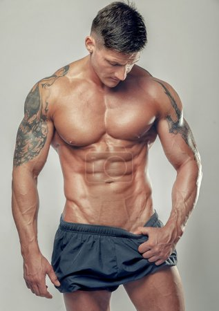 Photo for Strong muscular man bodybuilder poses and shows his muscles - Royalty Free Image