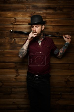 Man with tatto smokes and holds walking stick