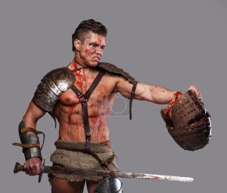 Photo pour Gladiateur couvert de sang tenant la tête coupée dans sa main - image libre de droit