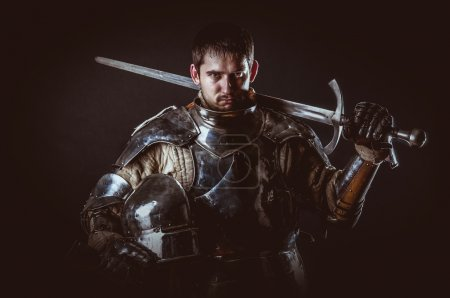 Photo for Powerful heavy fighter with sword and helmet - Royalty Free Image