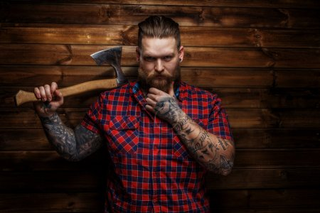 Photo for Huge brutal man with beard and tattooes holding axe - Royalty Free Image