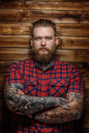Foto de Gran hombre brutal con barba y tatuaje - Imagen libre de derechos