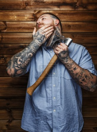 Huge brutal male with tattooes shaves his beard