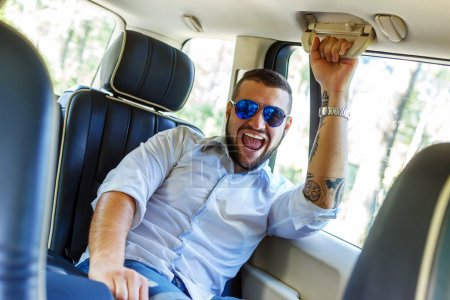 Happy male wit beart and tattoe in a car.