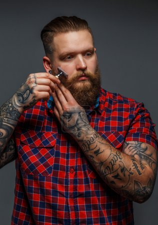 Brutal tattooed male shawing his beard