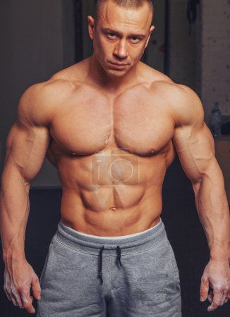 Bodybuilder poses and shows his muscles