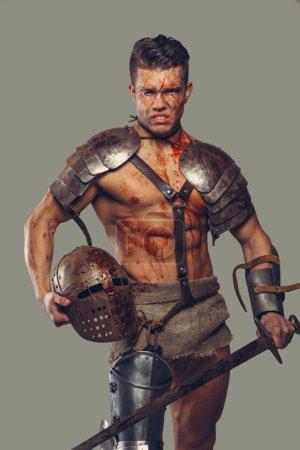 Photo pour Gladiateur avec corps musculaire recouvert de sang avec épée et casque - image libre de droit