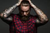Muž s tetováním na zbraně ve studiu