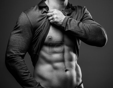 Photo for Muscular guy poses showing his abs and muscular body - Royalty Free Image