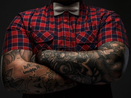Photo for Portraite of brutal hipster with tattooes on his hand dressed in red shirt and bow tie. - Royalty Free Image