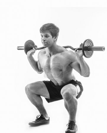 Photo for Young muscular guy in black shorts doing exercises with barbell. Isolated on white - Royalty Free Image