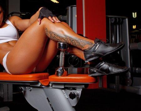 Photo pour Partie du corps femmes jambes avec tatouage dans une salle de gym - image libre de droit