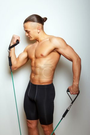 Muscular man doing exercises with expander