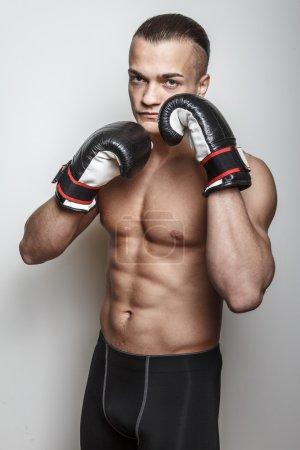 Photo pour Combattant musculaire dans des gants de boxe sur le fond blanc - image libre de droit