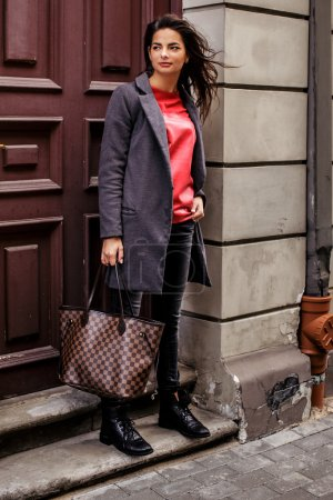 Photo pour Fille en veste grise debout près de l'entrée du bâtiment - image libre de droit