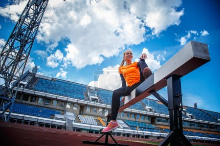 Photo for Female in sportswear doing exercises on the stadium. - Royalty Free Image