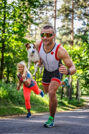 Photo for Smiling sportsman in sunglasses on the run with small dog in his hand. Running woman on background. - Royalty Free Image