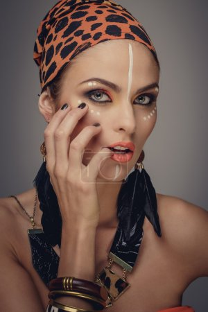Attractive woman with exotic make up posing on camera with hands near her face.