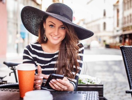 Photo pour Jeune femme souriante en chemise noire à rayures blanches et grand chapeau d'été noir assis à la table dans un café d'été . - image libre de droit