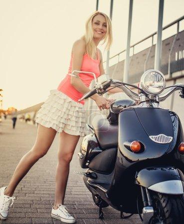 Slim smiling blond woman in short skirt