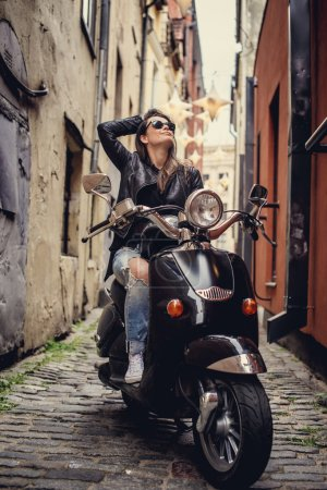 Photo for Casual woman with long brown hair sitting on moto scooter in old town's street. - Royalty Free Image