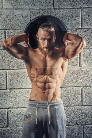 Shirtless muscular athlete guy holding weights.