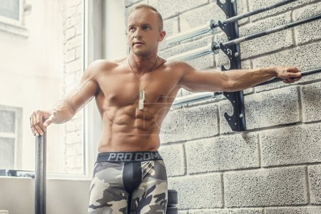 Young shirtless man posing near wall.
