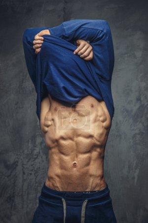 Muscular guy undressing blue shirt