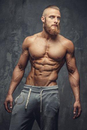 Shirtless bodybuilder with beard.