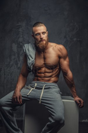 Portrait of muscular shirtless man with beard.