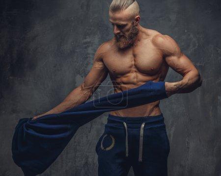 Muscular man undressing