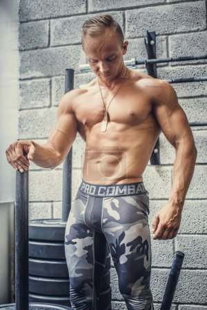 Shirtless guy in army pants.