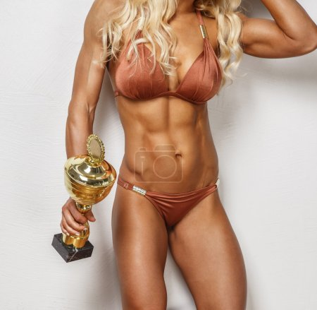 Photo for Woman's muscular body in underwear. Cup in a hand. - Royalty Free Image