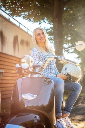 Photo pour Femme blonde en vêtements décontractés posant sur scooter moto sur fond d'arbres verts . - image libre de droit
