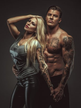 Photo for Awesome blond woman posing with shirtless muscular tattooed man. Isolated on brown background. - Royalty Free Image