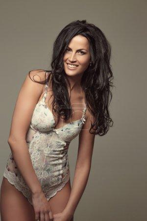 Photo pour Belle femme avec de longs cheveux noirs en sous-vêtements posant sur fond gris . - image libre de droit