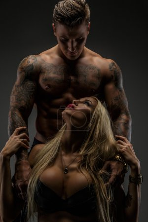 Photo for Modern couple of shirtless tattooed man and sexy blond woman in bra. Isolated on grey background. - Royalty Free Image
