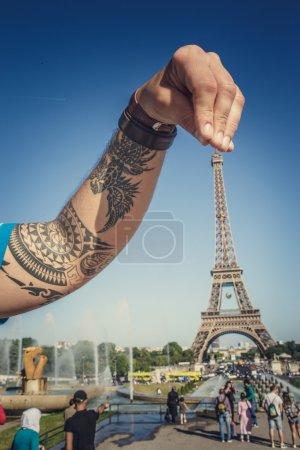 Tattooed arm abover eifel towe.