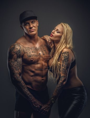 Tattooed man and woman posing.