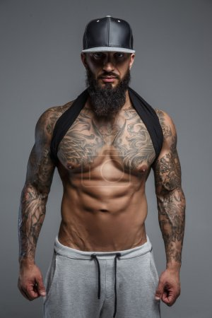 Shirtless tattooed man in black cap.