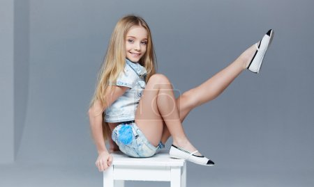 Photo for Blond littel girl in shorts and blue shirt posing on white chait in studio. - Royalty Free Image