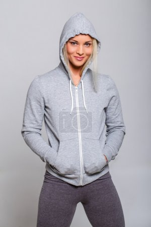 Athletic fitness woman in grey hoodie.