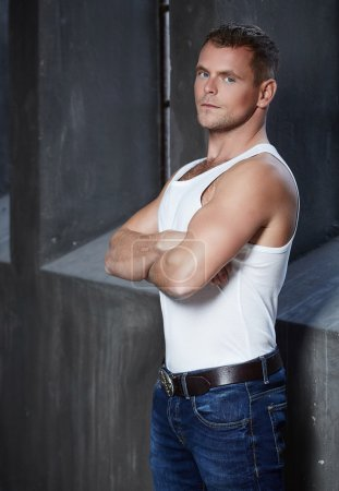 Photo for Attractive brutal man model in blue jeans and white t shirt. - Royalty Free Image