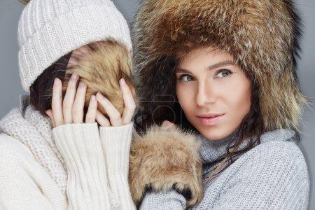girls in winter fur hats.