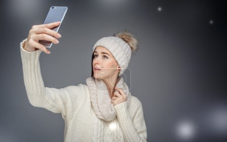 A woman in winter clothes taking picture  with herself on smartphone.