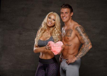 Foto de Hermosa pareja de hombre tatuado musculoso sin camisa y sensual mujer rubia sonriente. Corazón en las manos. Día de San Valentín - Imagen libre de derechos