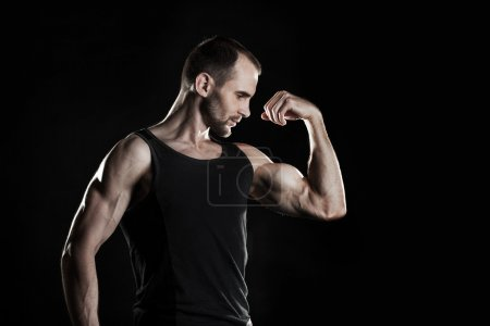 muscular man,  shows his biceps, black background, place for text on the right