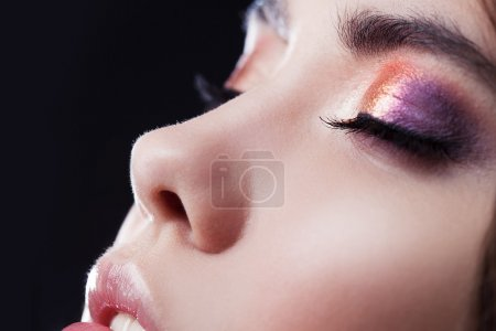 Close-up face, bright eye shadow, makeup. Shallow depth of field, black background