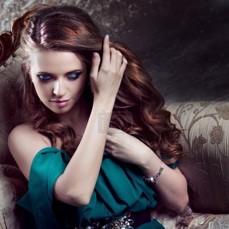 Beautiful  healthy luxurious hair, close-up. Young attractive woman in green dress sits on a beautiful sofa